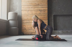 Young woman with yoga instructor in fitness club, lotus pose royalty free stock image
