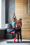 Young woman with yoga instructor in fitness club, tree pose Stock Images