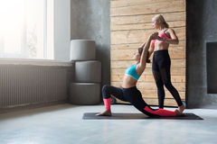 Young woman with yoga instructor in fitness club, warrior pose Stock Image
