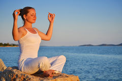 Young woman during yoga meditation on the beach. Over the blue sky Stock Photos
