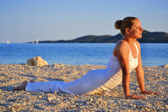 Young woman during yoga meditation on the beach. Young caucasian woman during yoga meditation on the beach Royalty Free Stock Image