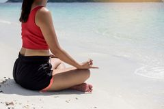 Young woman Yoga meditation on beach. relaxing sitting in water. In tropical summer travel Stock Images