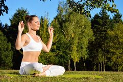 Young woman during yoga meditation in the park Royalty Free Stock Images