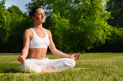 Young woman during yoga meditation in the park Royalty Free Stock Image