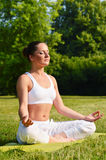 Young woman during yoga meditation in the park Stock Photography