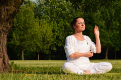Young woman during yoga meditation in the park Royalty Free Stock Photos