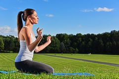 Young woman during yoga meditation in the park royalty free stock photography