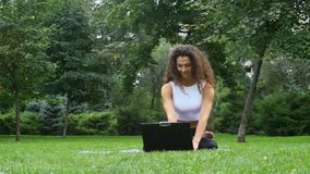 Young woman yoga in the park working on a laptop stock video