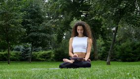 Young woman yoga in the park working on a tablet stock video
