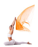 Young woman in yoga pose and flying fabric Stock Image