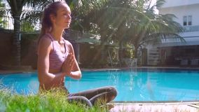 Young woman in yoga pose folds hands in prayer side view. Young attractive woman in Lotus position meditates folding hands in prayer by small pool against waving stock video