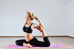 Young woman in yoga position indoors Stock Photos