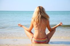 Young woman during yoga on sea beach Stock Photography