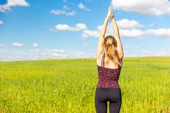 Young woman yoga stretching rear view. royalty free stock image
