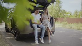 Young woman with young guy relax and talking inside the car trunk. Happy in love couple sit inside th trunk of the car and talking. Young girl and guy have a stock footage