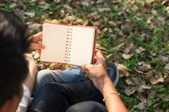 Young woman and young man hugging and holding notebook  Together. Young woman and young man hugging and holding notebook Together sitting in public garden autumn Royalty Free Stock Photo
