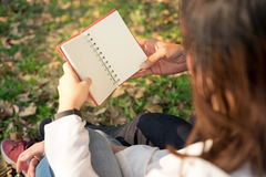 Young woman and young man hugging and holding notebook  Together. Young woman and young man hugging and holding notebook Together sitting in public garden autumn Stock Photo