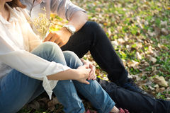 Young woman and young man huging and holding bouquet white flowe. R sitting in public garden autumn season background Royalty Free Stock Photography