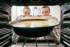 Young woman and young man looking at cheesecake into oven royalty free stock photography