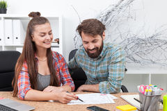 Young woman and young man in office environment Stock Photo