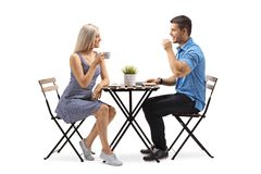 Young woman and a young man sitting at a coffee table royalty free stock photography