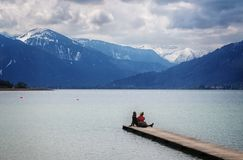 Young woman and young man sitting together on the jetty in the t Stock Photos