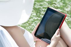 Young woman with your tablet in hand. Young woman with your tablet in white hat on nature Royalty Free Stock Photography