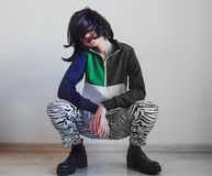 Young woman in zebra print and 90s clothes. Sitting on a floor stock photos
