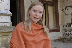 Young womanan Looking Forward With Anticipation. Young blonde woman with blue eyes Looking Forward With Anticipation in old castle, in orange poncho Stock Photos