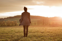 Young womanl is standing on the meadow. Portrait of a young woman is standing on the meadow and watching the sunset enjoying nature summer evening outdoors. Soft royalty free stock image