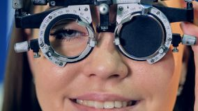 Young womans eyes covered by a medical trial frame. A close-up view on womans eyes as she puts on a trial frame stock video footage