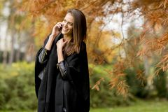 Young womanusing mobile phone in autumn park Stock Images