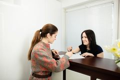 Young woman administrator in a dental clinic in the workplace. Admission of the client stock photography