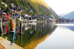 Young women admiring the famous Hallstatt town one autumn morning. royalty free stock image