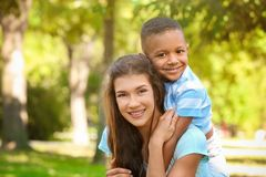 Young woman with adopted African American boy. Young women with adopted African American boy outdoors Royalty Free Stock Image