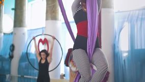 Young women air gymnasts making gymnastic elements in a studio. Slow motion stock video