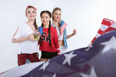 Young women with american flag looking at camera and drinking beverages Stock Photo