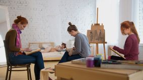 Young women artists painting picture in art studio