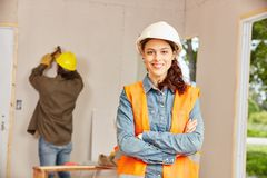 Young woman as apprentice of craftsman. Young women as apprentice of craftsman working at construction site stock images