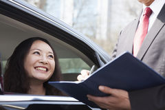Young women in back seat of car talking with business colleague. Stock Images