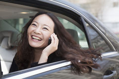 Young women in back seat of car using mobile phone. Royalty Free Stock Photo