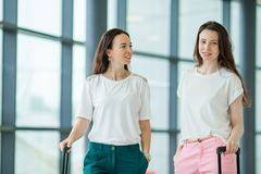 Young women with baggages in international airport. Airline passengers in an airport lounge waiting for flight aircraft. Young women in international airport Stock Photos