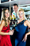Young women and bartender in club or Bar Stock Photography