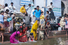 Young women bath in the Ganges River on steps of Ghat. Royalty Free Stock Images