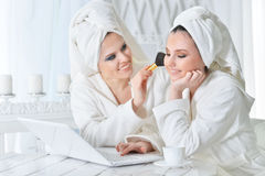 Young women in bathrobes with laptop Royalty Free Stock Photography