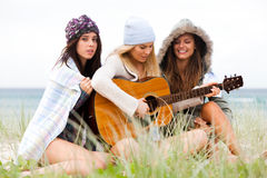 Young Women at the Beach With a Guitar Stock Images