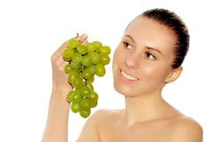 Young women with beautiful face a. Portrait of young women with beautiful face and green grapes stock photography