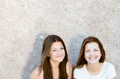 2 young women beautiful girl friends happy smiling. Young women beautiful girl friends standing at grey wall smiling & looking at camera Royalty Free Stock Photography