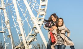 Young women best friends enjoying time together with piggyback at luna park ferris wheel Stock Photo