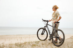 Young women with bicycle. Looking at see Stock Image
